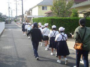 1列で整列して移動調査する児童