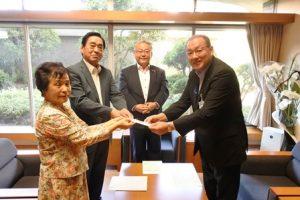 浦上市議会議長立会いの下、収益金を菅野教育長に渡す小西代表と小橋会長