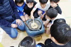 火鉢で豆を炒る児童