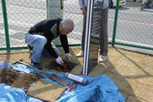 芝生を剥ぎ、カプセルを埋める穴を掘る。